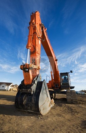 Backhoe at a construction site stock photo, Large orange backhoe at a construction site by Steve Mcsweeny