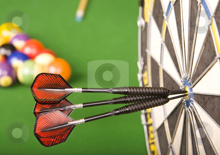 Games room stock photo, Three darts in a dart board with a pool game in the background, games room. by Steve Mcsweeny