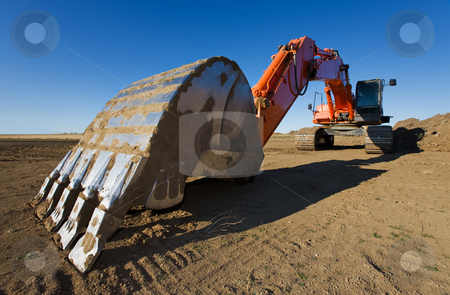 Backhoe stock photo, A large orange backhoe parked at a construction site by Steve Mcsweeny