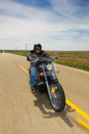 Bike ride stock photo, A biker taking a ride on a long strait rural road by Steve Mcsweeny