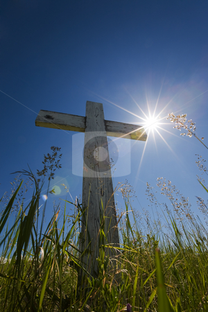 Grave in sunlight stock photo, Old wooden cross in a graveyard with sun flares by Steve Mcsweeny