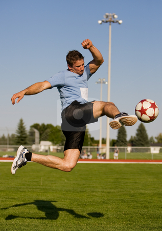 Soccer kick stock photo, Athletic male in the air kicking a soccer ball by Steve Mcsweeny