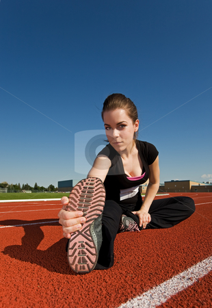 Stretch stock photo, A beautiful woman stretching before a race at the track by Steve Mcsweeny