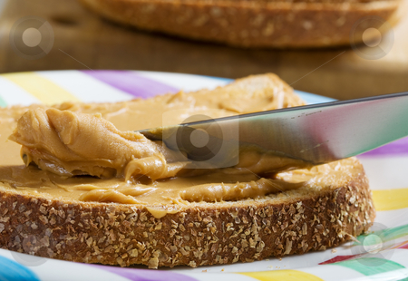 Peanut butter spread stock photo, A macro shot of peanut butter being spread on whole wheat bread by Steve Mcsweeny