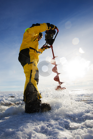 Ice drilling stock photo, Ice fisherman drilling a hole with a power auger with sun flares by Steve Mcsweeny