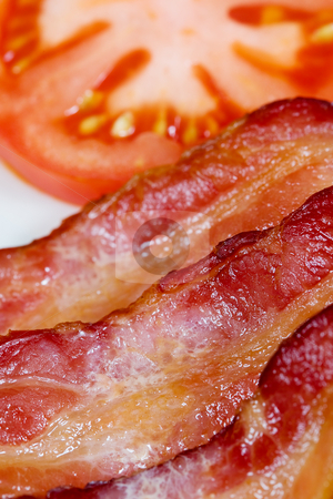 Bacon stock photo, A close up view of bacon with a tomato in the background by Steve Mcsweeny