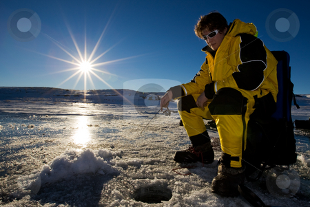 Sunset fishing stock photo, Fisherman enjoying a day on the ice with a low setting sun by Steve Mcsweeny