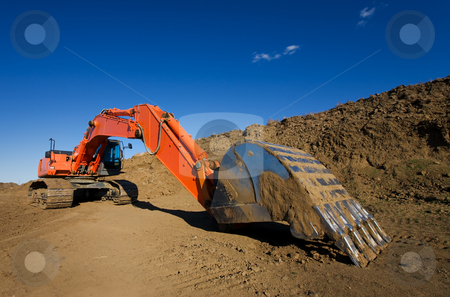 Construction site stock photo, A large orange backhoe at a construction site by Steve Mcsweeny