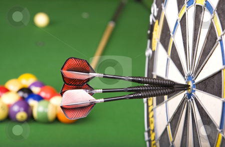 Games stock photo, Darts in a dart board with a pool game in the background(shallow dof) by Steve Mcsweeny