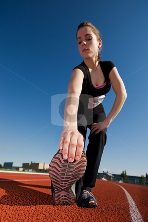 Stretching stock photo, A beautiful woman athlete stretching before a race (main focus on shoe) by Steve Mcsweeny