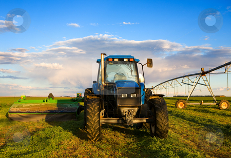 Farm tractor stock photo, Farm equipment in the field with blue sky and clouds by Steve Mcsweeny