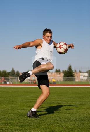 Kicking a soccer ball  stock photo, Athletic male kicking a soccer ball outside by Steve Mcsweeny