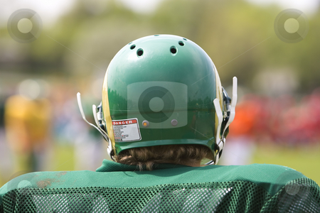 American football player stock photo, American football player watching his team from the sidelines by Steve Mcsweeny