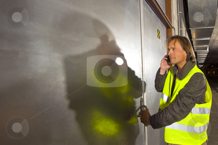 Tunnel Engineer stock photo, A man with a phone in his hand wearing a yellow reflective safety vestopening a steel door inside a tunnel by Corepics VOF