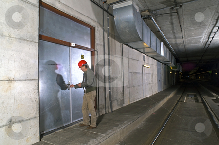 Unlocking a door stock photo, A man with a hard hat in his hand unlocking a steel door inside a tunnel by Corepics VOF