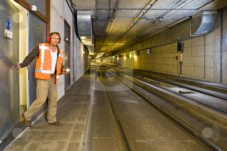 Tunnel Engineer stock photo, A sturdy looking engineer, closing a door to a maintance room behind him inside a public transportation tunnel, looking relaxed and with a flashlight in his hand by Corepics VOF