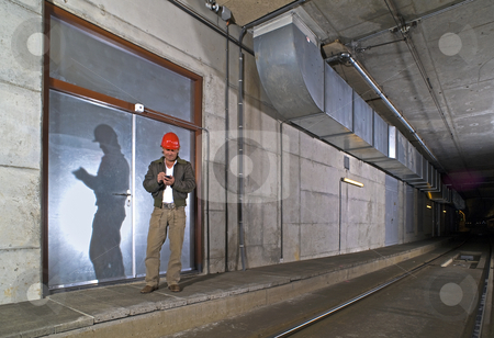 Engineer with PDA stock photo, An Engineer in a dimly lit public transportation tunnel checking his Personal Digital Assistant by Corepics VOF