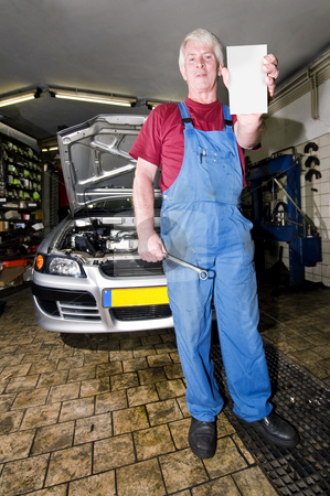 Motor Mechanic stock photo, A senior motor mechanic, holding up a blank cart with a wrench in his hands, posing in front of the car he's been working on by Corepics VOF