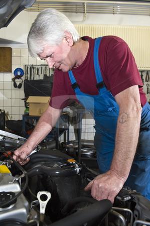 Car Mechanic stock photo, A senior motor mechanic servicing a car inside a garage by Corepics VOF