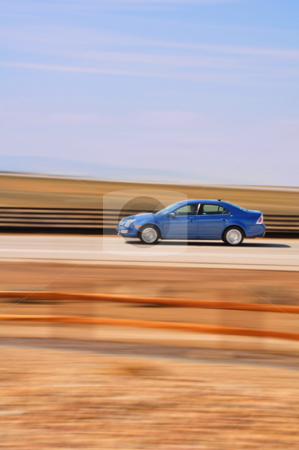Blue Car with Motion Blur stock photo, A blue sedan speeds by with intentional blur due to the motion. by Ben O'Neal