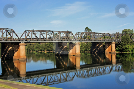 Victoria Bridge stock photo, An old but still operable iron railway bridge erected over a river, complete with reflection. by Adam Goss