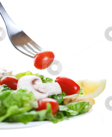 Salad With Fork stock photo, A cherry tomato on a fork above a freshly tossed salad.  Shot on white background.  Shallow depth of field. by Brenda Carson