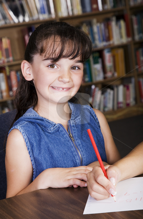 Child in School Library stock photo, A child smiling from her desk in the school library. by Brenda Carson