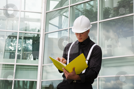 Foreman With File stock photo, A foreman checks his blueprints outside of city hall. by Brenda Carson
