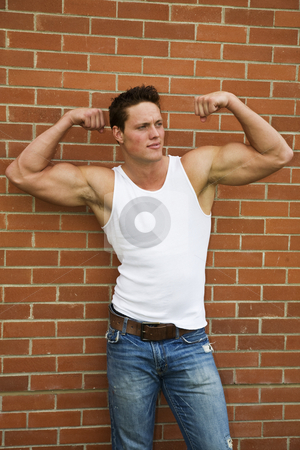 Flexing Bodybuilder stock photo, A young bodybuilder flexing his arms to show off his muscles. by Brenda Carson