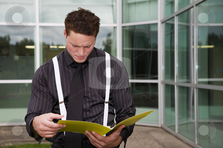Concentrating on Business stock photo, A businessman concentrating on the paperwork in his folder. by Brenda Carson