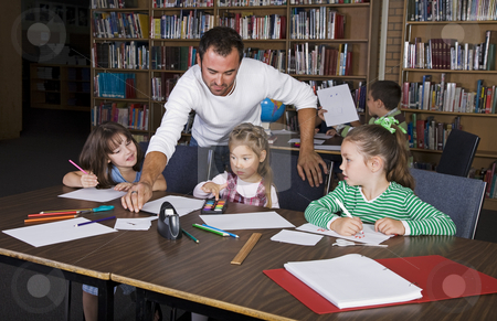 Grade School stock photo, A teacher with his elementary students in the school library. by Brenda Carson