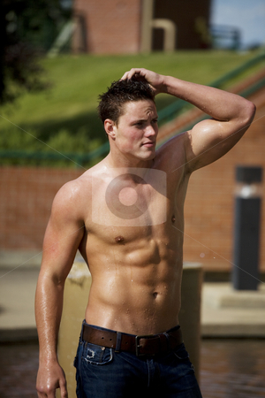 Wet Male Model stock photo, A young bare chested man cooling off in the water, on a hot summer day. by Brenda Carson