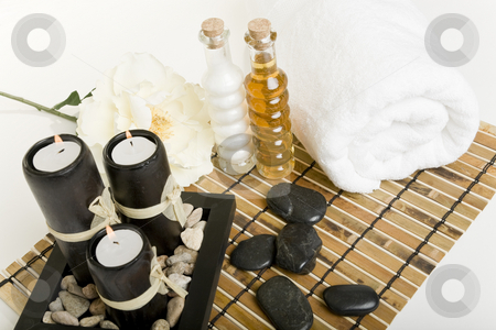Spa & massage products stock photo, The candles are lit & massage stones, oils, & a towel are all laid out in preparation for a spa treatment. by Brenda Carson