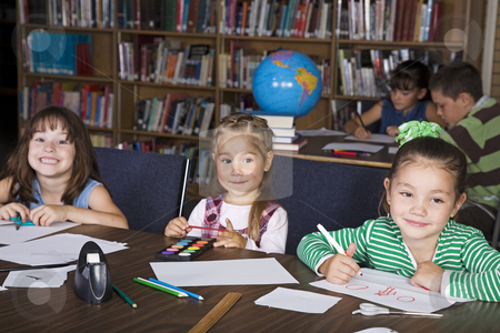 Kids at School stock photo, Elementary students in a school library doing art projects. by Brenda Carson