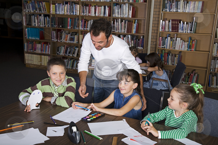 Learning in the Library stock photo, A teacher with his elementary students in the school library. by Brenda Carson