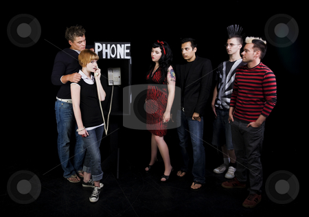 Waiting For The Phone stock photo, Six teenagers in a high school play.  A group of teenagers wait for their turn to use a public phone, while another girl hogs it. by Brenda Carson