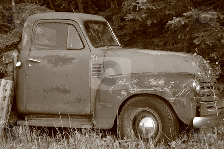 Old Grunge Truck stock photo, Heavily scratched and weather-beaten , grungy old truck.  It has been abandoned for so long that grass and sapling trees have grown up around it. by Brenda Carson