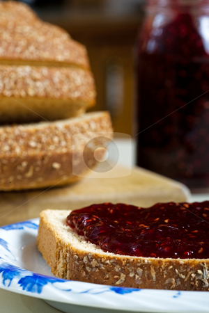 Bread and Jam stock photo, A thick layer of tangy raspberry jam, on whole wheat multi-grain bread.  Focus on bread. by Brenda Carson