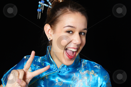 Peace in Any Language stock photo, Mixed race girl in oriental dress flashes a big smile as she gives a peace sign. by Brenda Carson