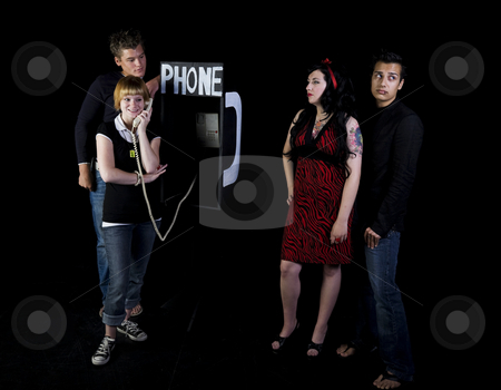 School Play stock photo, Four teenagers in a high school play.  A girl & her boyfrind wait for their turn to use a public phone while another girl chats away. by Brenda Carson