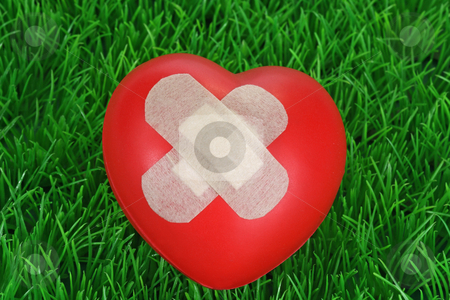 Red heart stock photo, Red heart with plaster on green background by Birgit Reitz-Hofmann