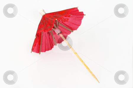 Cocktail umbrella stock photo, Red cocktail umbrella on bright background by Birgit Reitz-Hofmann