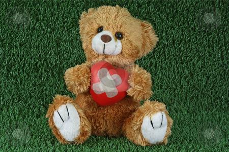 Love sick stock photo, Cute teddy bear with decorative heart on green background by Birgit Reitz-Hofmann