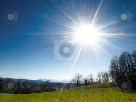 Meadow under spring sun stock photo, Meadow under spring sun with mountains on the background by Laurent Dambies