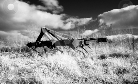 Infrared plough machine stock photo, Infrared picture of a plough machine  on field with dramatic sky by Laurent Dambies