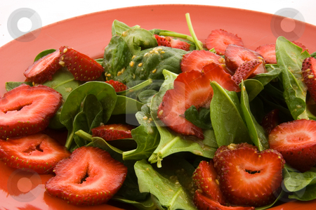 Spinach and Strawberry Salad stock photo, This closeup is of a fresh spinach and strawberry salad on a red plate.  Also has sesame seeds and garlic for a delicious side entree. by Valerie Garner