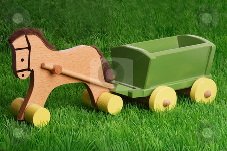 Wooden toy stock photo, Horse wooden toy on green grass background by Birgit Reitz-Hofmann