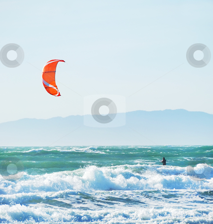 Kite Surfing in San Francisco California stock photo, Surfer with red kite surfing off the beach in San Francisco, California on a sunny day. by Denis Radovanovic