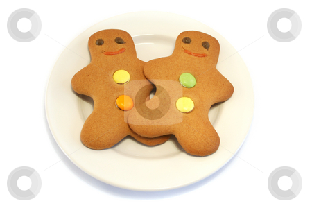 Two Gingerbread men on a Plate stock photo, Two Gingerbread men on a cream plate on a white background by Helen Shorey