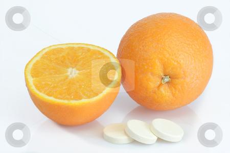 Vitamins_1 stock photo, Large pills with orange fruits tube on bright background by Birgit Reitz-Hofmann